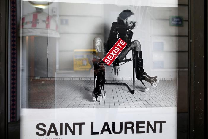 """A sticker which reads """"sexist"""" is seen on an ad by French fashion house Yves Saint Laurent displayed on a newspaper kiosk in Paris, France, March 6, 2017. France's advertising watchdog on Monday said it had asked French fashion house Yves Saint Laurent to modify two ads from its latest campaign after receiving 50 complaints that they were """"degrading"""" to women. REUTERS/Charles Platiau"""