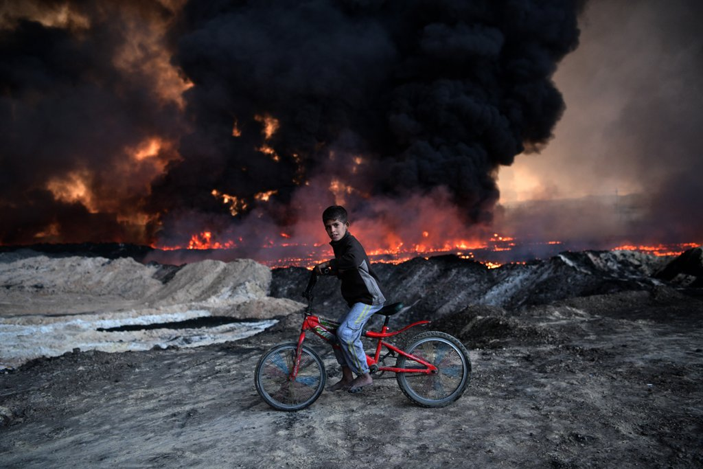 october-21-boy-passes-oil-field-set-fire-retreating-isis-fighters-qayyarah-iraq