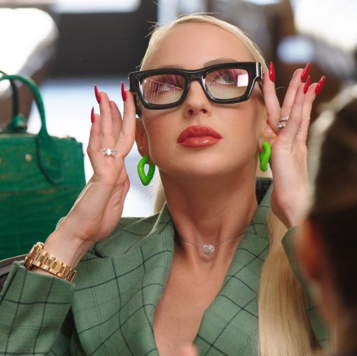 Quinn in a green Gucci dress and Louis Vuitton men's glasses.