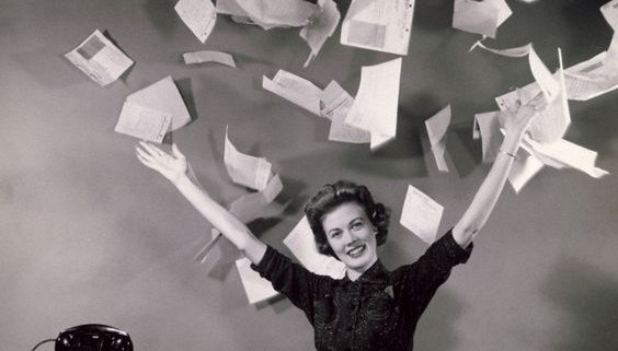 Businesswoman throwing papers in office --- Image by © SuperStock/Corbis