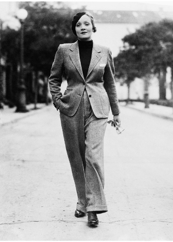 25 Jan 1933 --- Wearing a beret and carrying gloves, Marlene Dietrich, prominent Paramount screen star, jauntily strolls along Hollywood Street attired in a grey man's suit, with turtle-neck sweater. Stylists declare this mode set by Marlene will sweep the country--which probably means that men will have to find themselves some cute tailored skirts. --- Image by © Bettmann/CORBIS