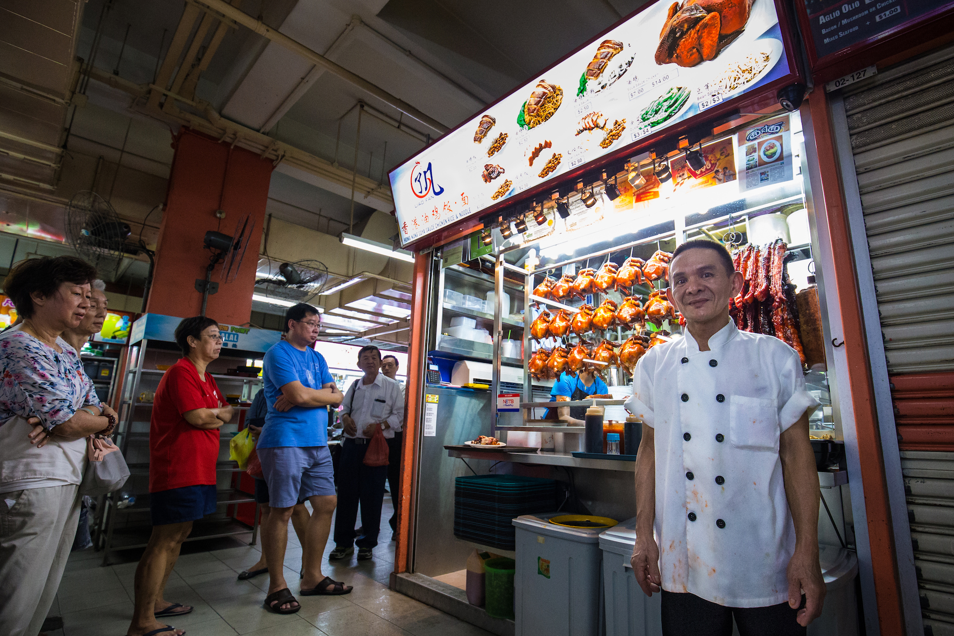 Chan Hong Meng poses for a photo at his Hong Kong Chicken Rice and Noodle stall at Chinatown Complex on July 24, 2016 in Singapore. Chan was awarded a one-star rating by Michelin on July 21, making him one of the first street food hawkers to be awarded in the guide's history.