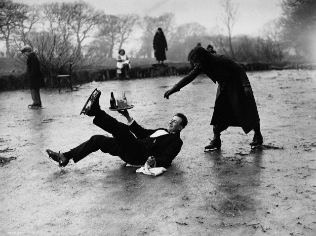 13 Feb 1936, London, England, UK --- An ice skating waiter manages to keep his tray upright after slipping on a frozen pond. His customers include people skating on the pond. Hampstead, London, England, February 13, 1936. --- Image by © Hulton-Deutsch Collection/CORBIS